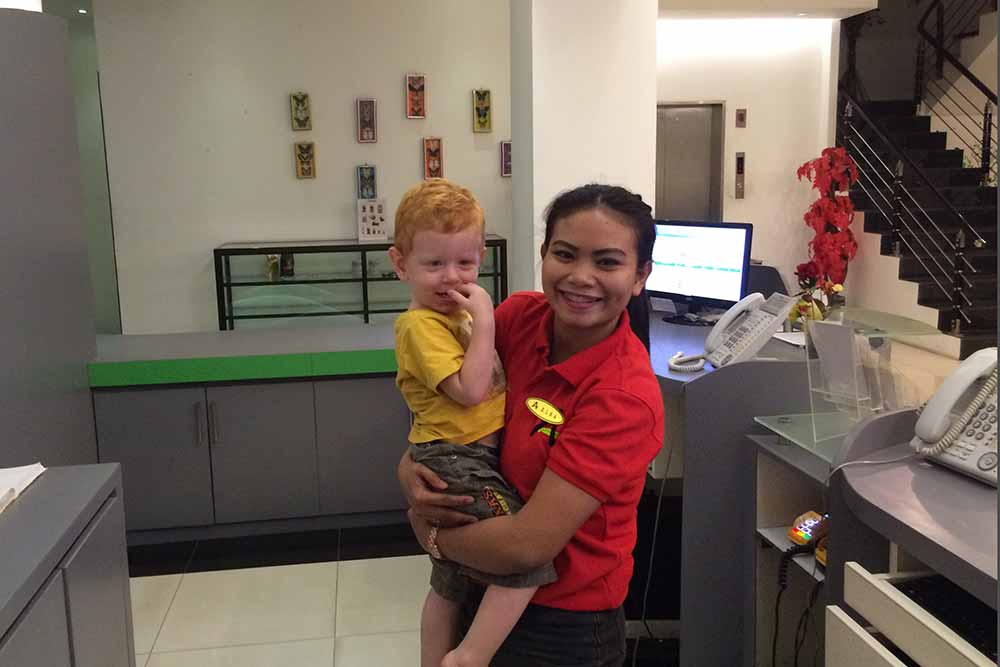 Jace with the receptionist at our second hotel in Makassar. Everybody loves our little world traveler