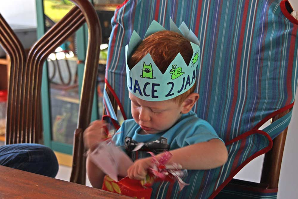 Jace opening his birthday presents in North Sulawesi while sitting in his Totseat