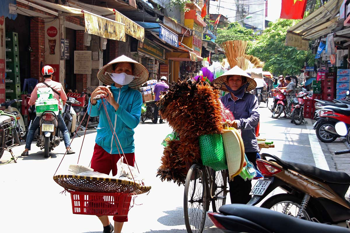 Yes, they actually wear the Vietnamese hats! In the streets you see a lot of street vendors, either carrying there wares like this lady on the left is doing, or transporting there goods by bike