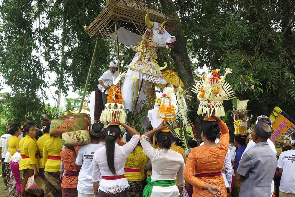 Local women carrying offerings for the deceased village priest on their heads to be added to the funeral pyre